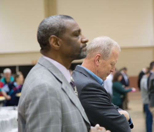 two men praying at a convention